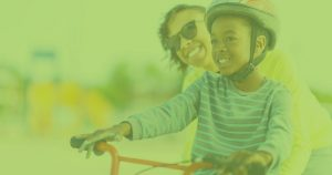 Green image with mom helping daughter ride a bike